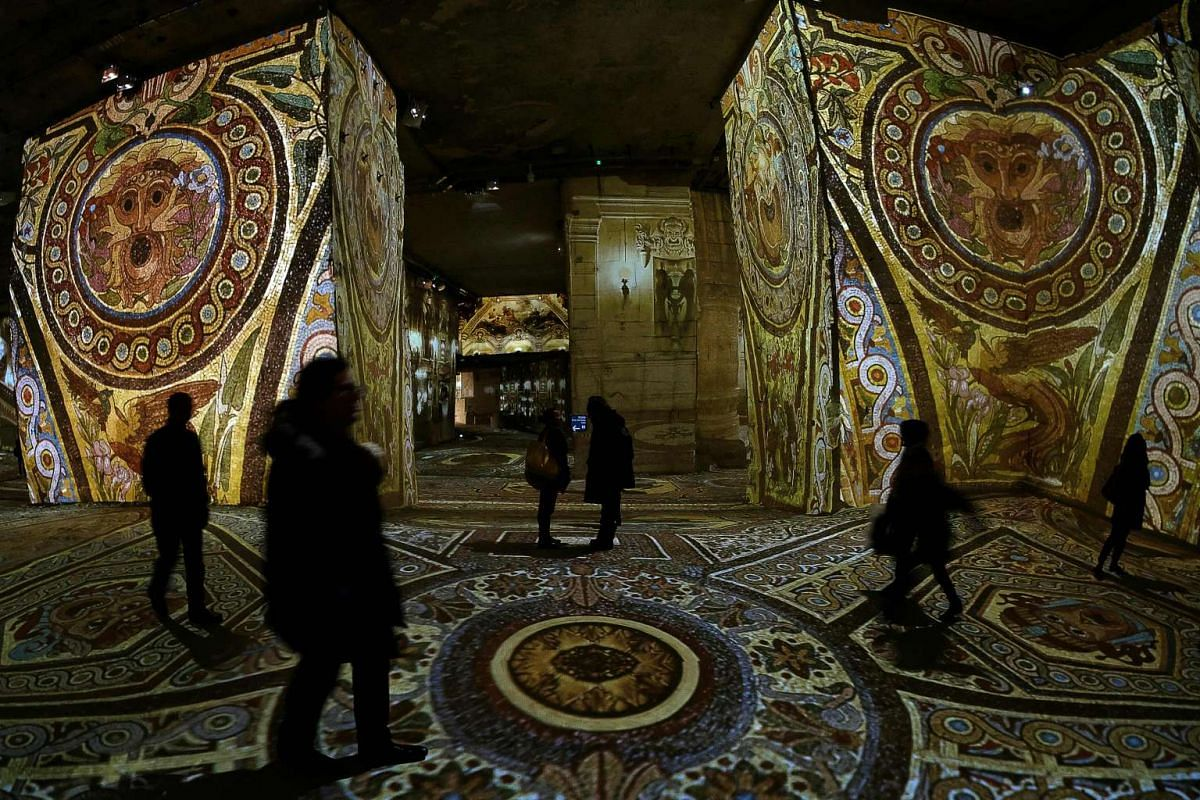 People looking at projections of works by late French painter Marc Chagall at the Quarries of Lights in Les Baux-de-Provence on March 3, 2016.