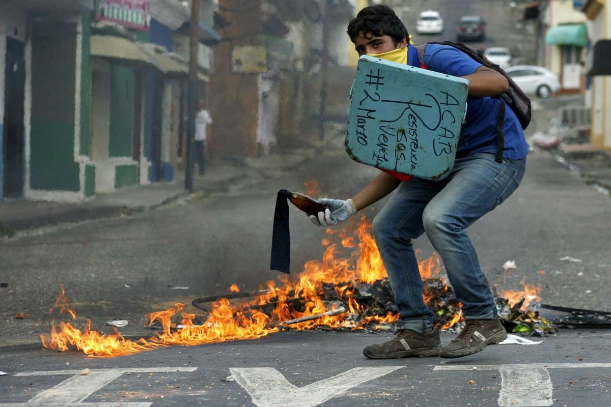 A student demonstrator preparing to throw a Molotov cocktail during clashes with the police during a protest against President Nicolas Maduro's government in San Cristobal, Venezuela, on March 2, 2016.