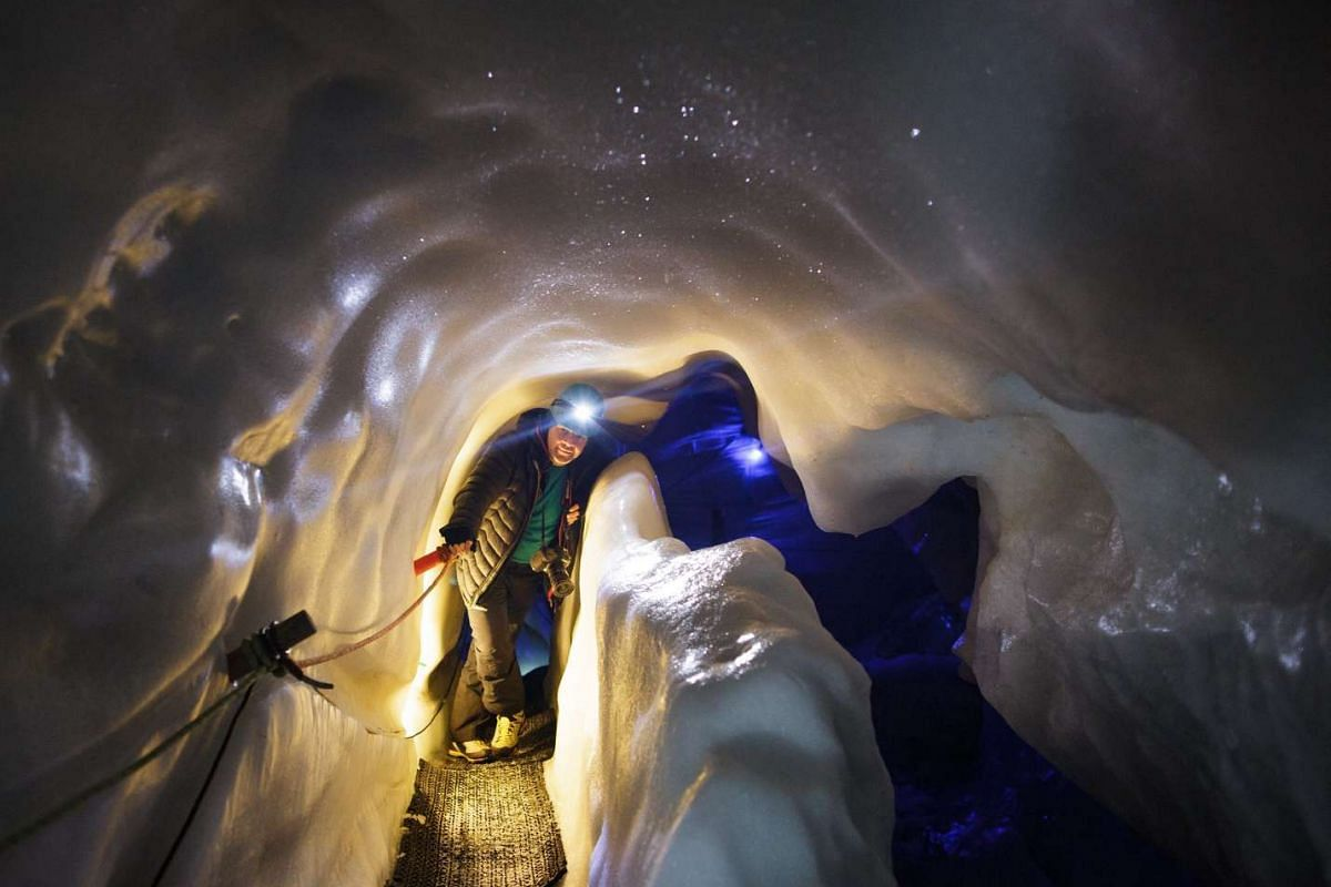 A tourist walks inside the Ice Palace glacier hollow at Hintertux glacier, located around 3250m above sea level, in Zillertal, Austria, on March 2, 2016.
