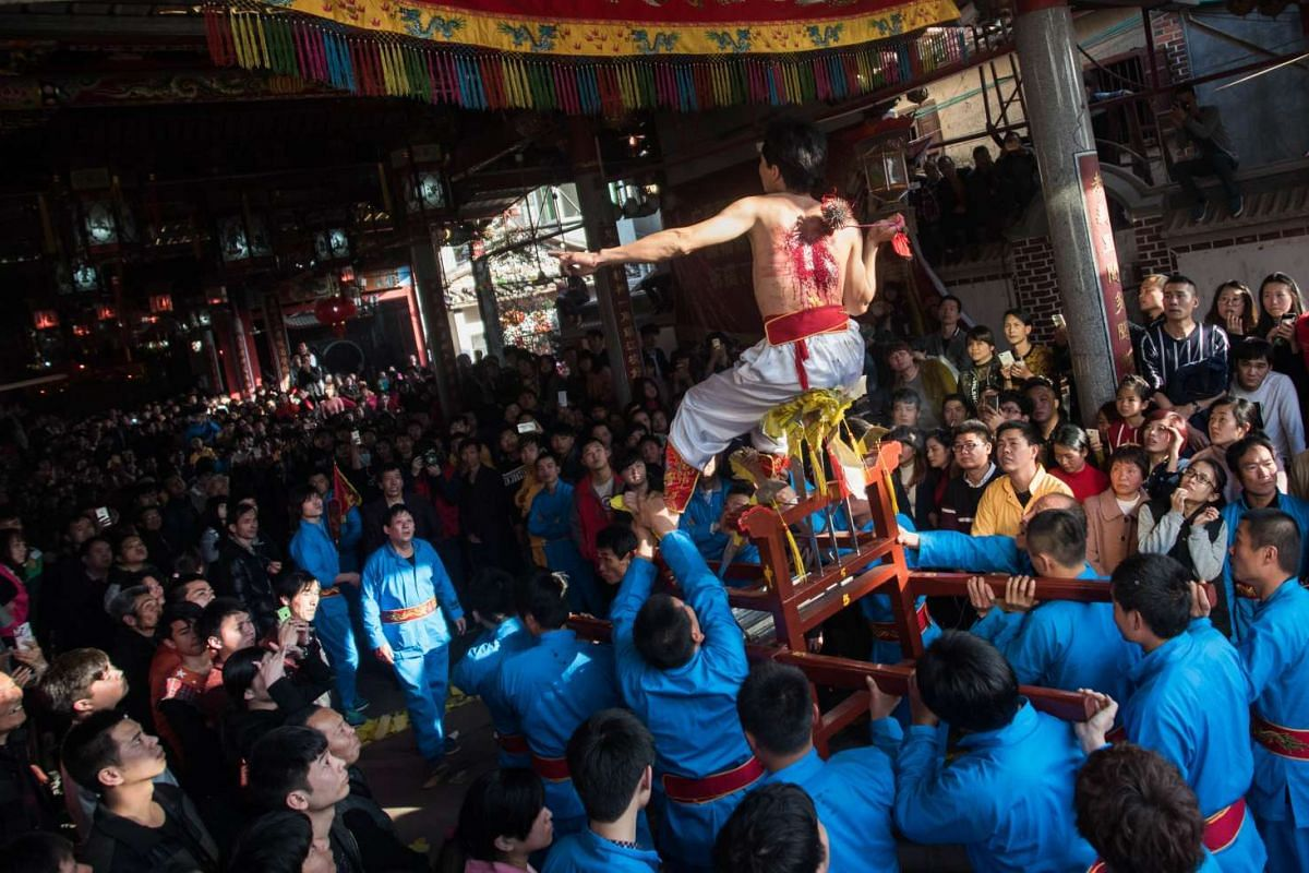 A young man flaying his back with a thorny iron during the 'Da Tiequ' (beat the iron ball) event in front of the Dalugong Temple in Zheqiancun village in Putian, south-east China's Fujian province, on March 2, 2016.