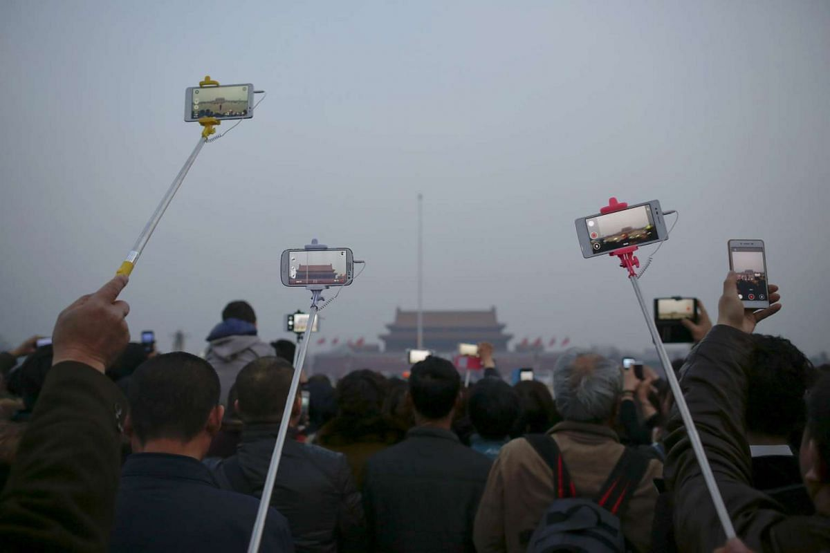 People using selfie sticks, mobile phones and cameras to record and take pictures of a flag-raising ceremony at Tiananmen Square in Beijing, China, on March 3, 2016.