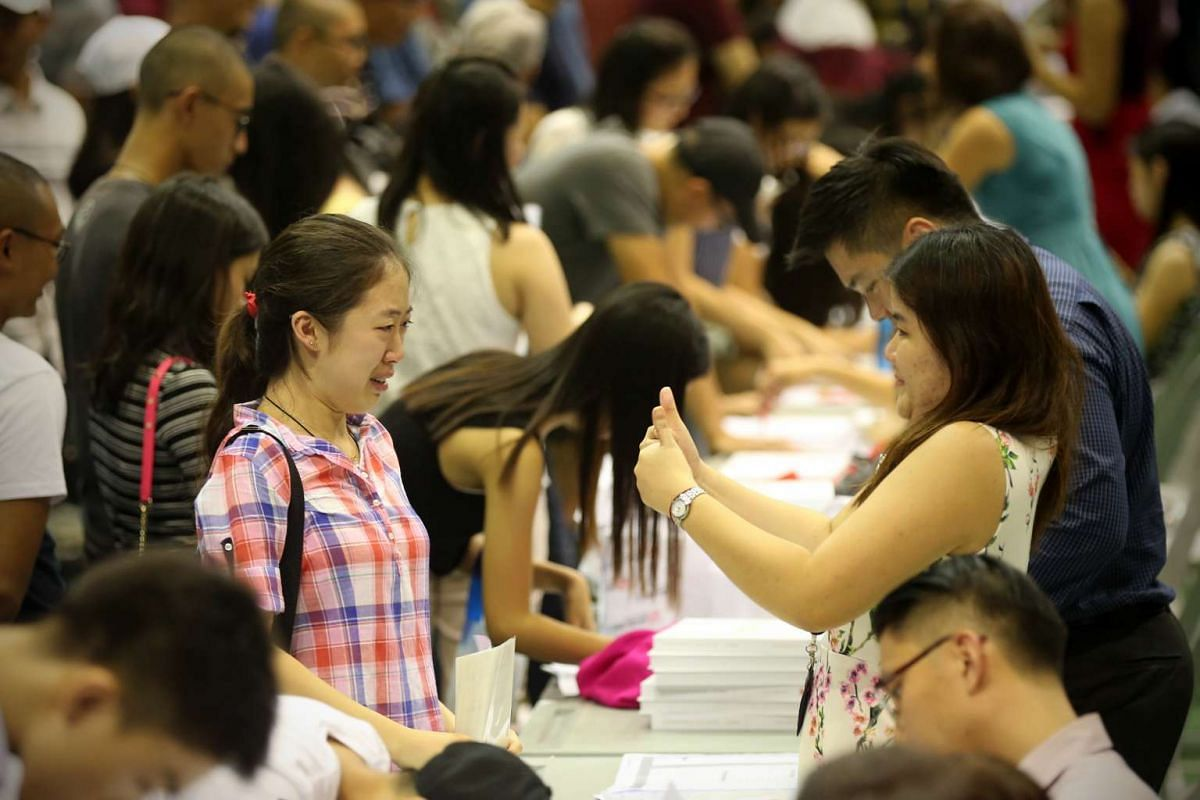 Civics tutor Mrs Violet Teo (right) gives a thumbs up to her student Ms Crystal Sia as she reacts emotionally after receiving good results in Hwa Chong Institution on March 4, 2016.