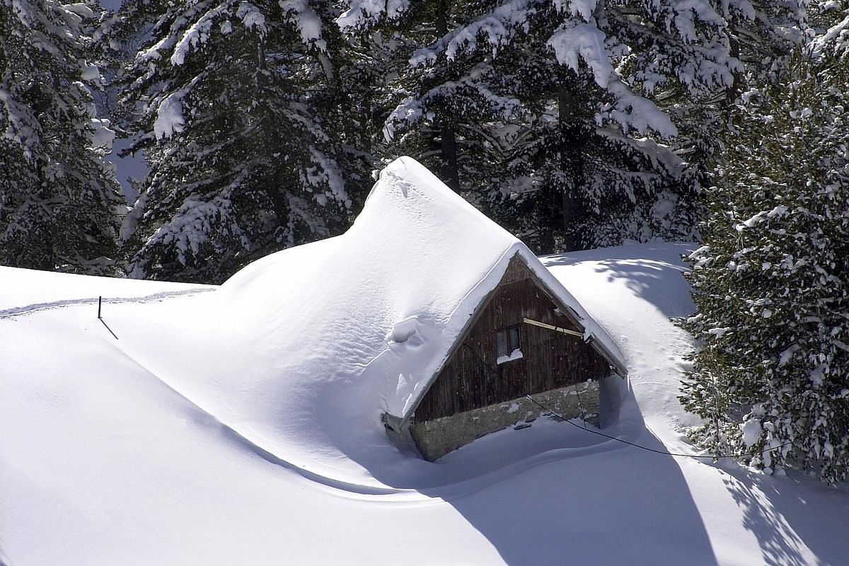 The rundown old resort of Brezovica offers steep slopes and deep, powdery snow. An old cabin (below) is nearly buried in snow.