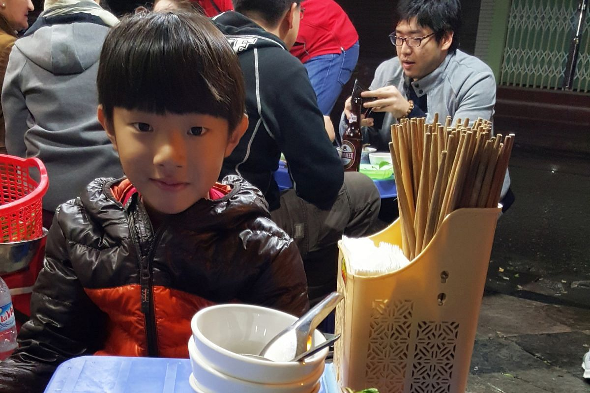 Writer Tan Keng Yao's son, BBC, eating at a streetside stall in Hanoi.