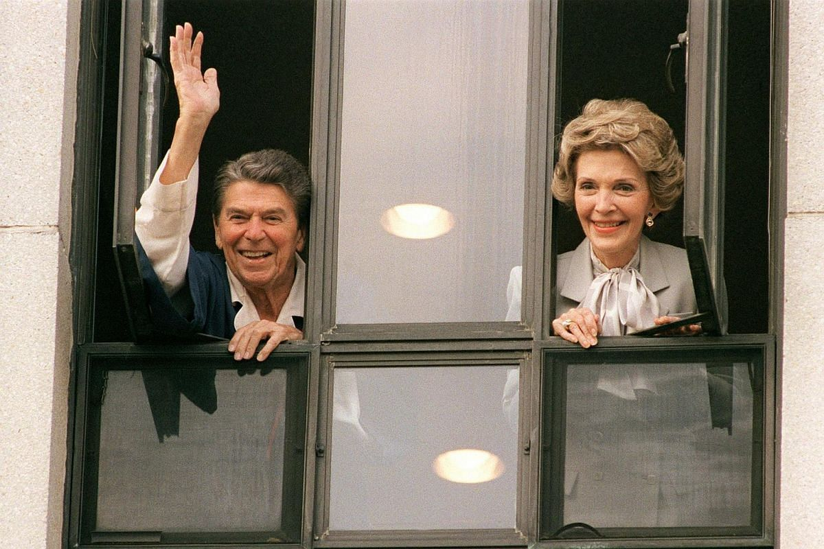 Former US President Ronald Reagan waving to the press from the window of his room at Bethesda Naval Hospital with First Lady Nancy Reagan.