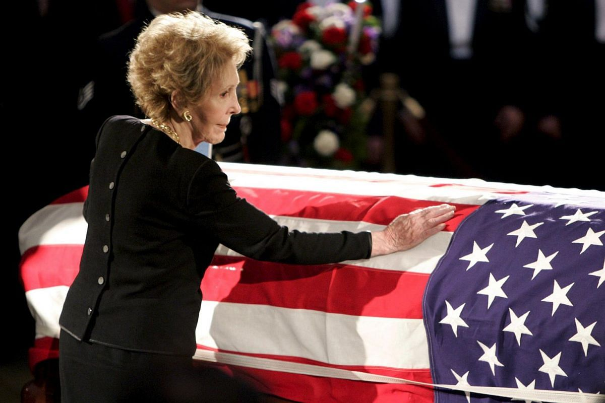 Mrs Nancy Reagan touches the casket of her husband, former US president Ronald Reagan, as it lies in state in the rotunda of the United States Capitol in Washington on June 9, 2004.