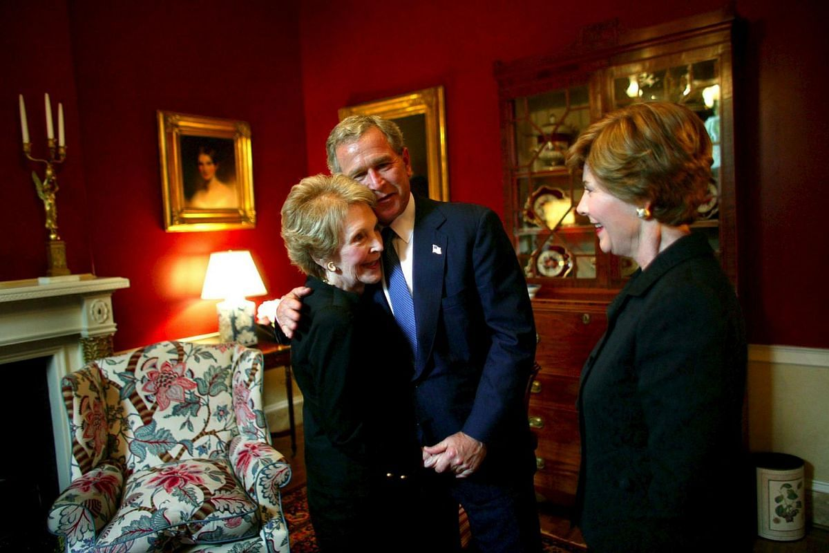 Then US President George W. Bush and First Lady Laura Bush (right) greet former first lady Nancy Reagan at Blair House in Washington on June 10, 2004.
