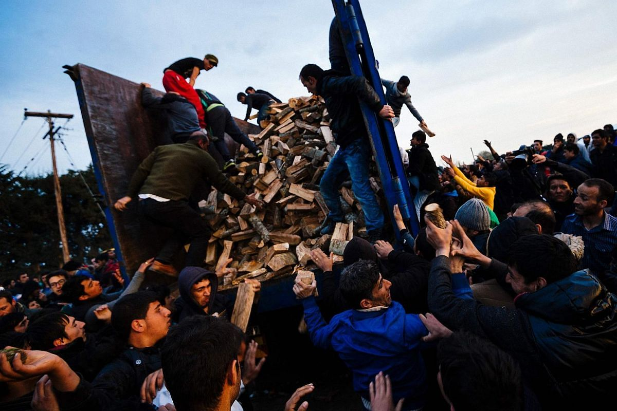 People rush to get firewood in a makeshift camp of the Greek-Macedonian border, on March 6, 2016.