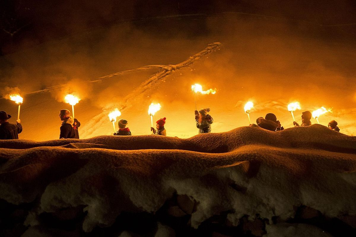 People walk with torches on the occasion of the Funkensonntag, in Appenzell, Switzerland on March 6, 2016.
