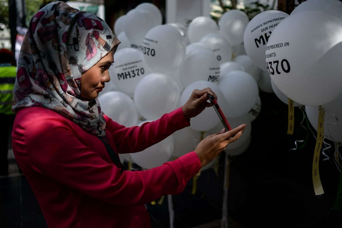 A woman takes pictures of balloons with MH370 written on them during a memorial event in Kuala Lumpur on March 6, 2016.