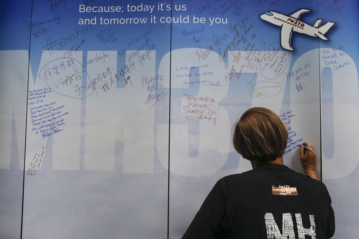 Blaine Gibson, who found possible plane debris in Mozambique last month, writes messages for the passengers of missing Malaysia Airlines flight MH370 on a banner during a remembrance ceremony to mark the second anniversary of the plane's disappearanc
