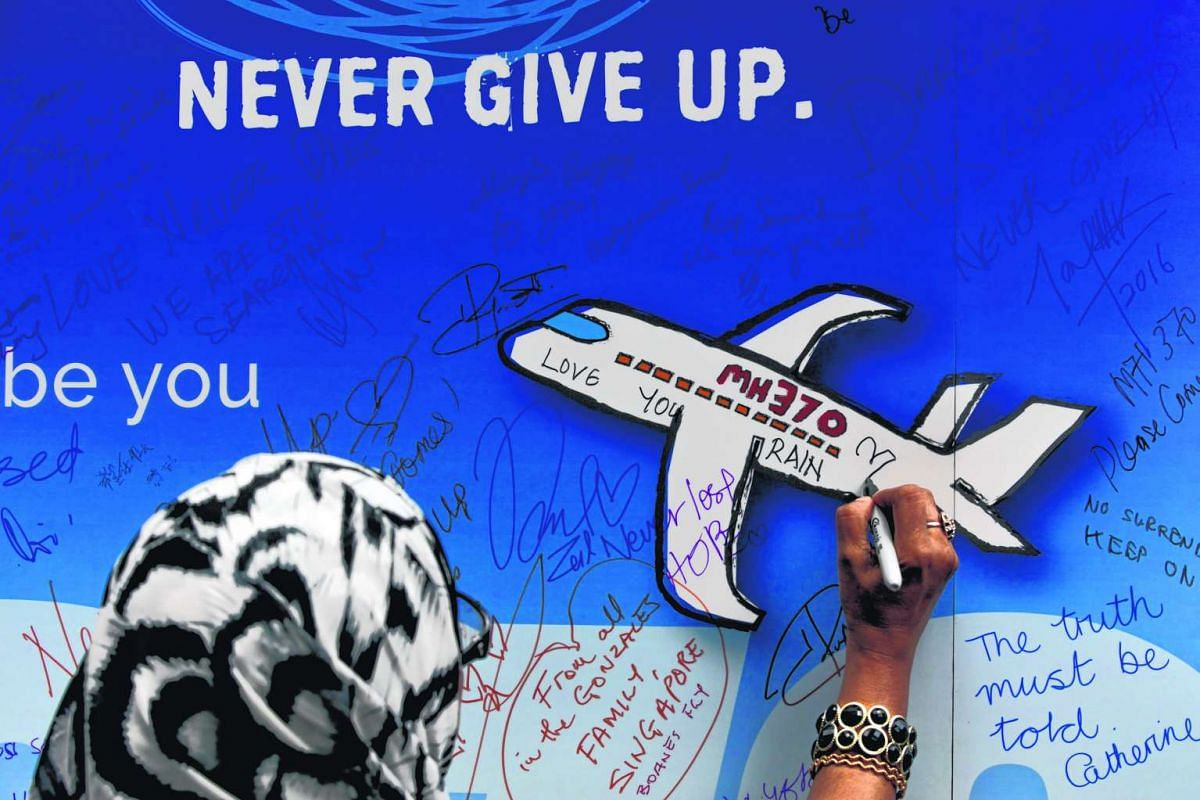 A woman writes messages for the passengers of missing Malaysia Airlines flight MH370 on a banner during a remembrance ceremony to mark the second anniversary of the plane's disappearance, in Kuala Lumpur, Malaysia, on March 6, 2016.