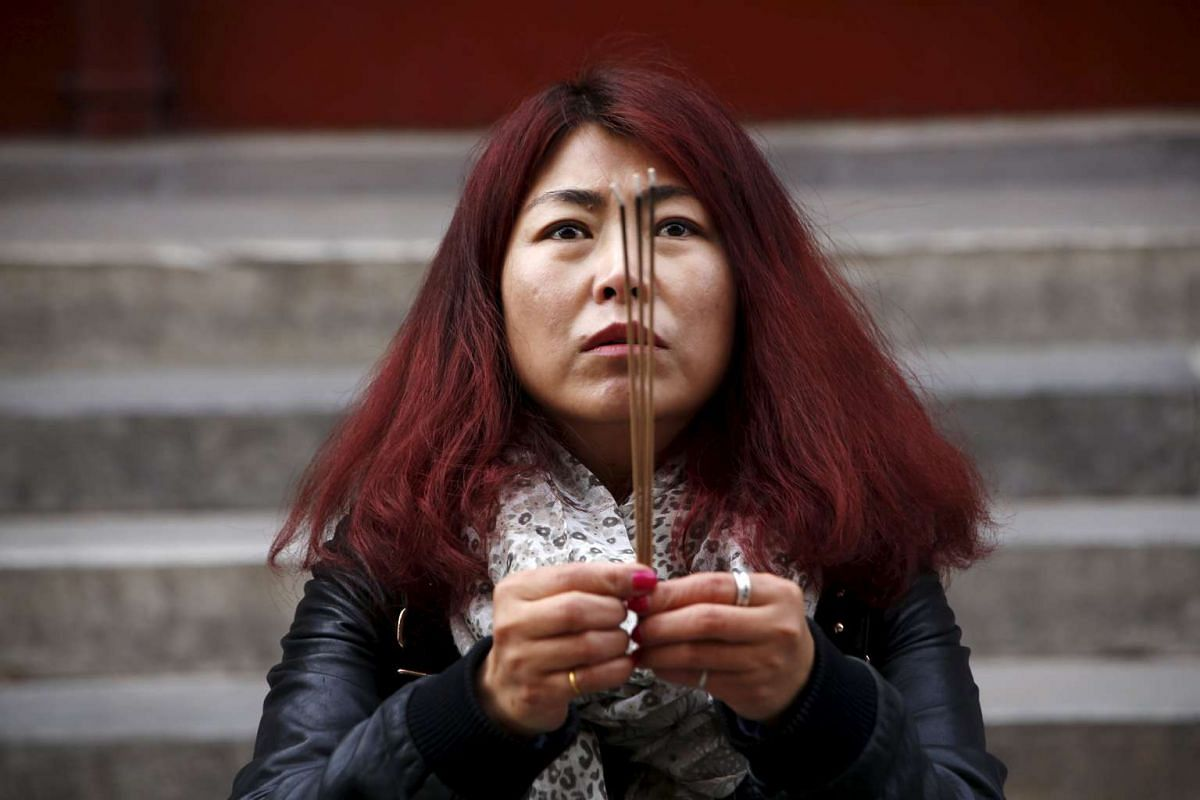 Cheng Liping prays for her husband Ju Kun who was on board Malaysia Airlines flight MH370 which went missing in 2014, at Lama Temple in Beijing, China, on March 8, 2016.