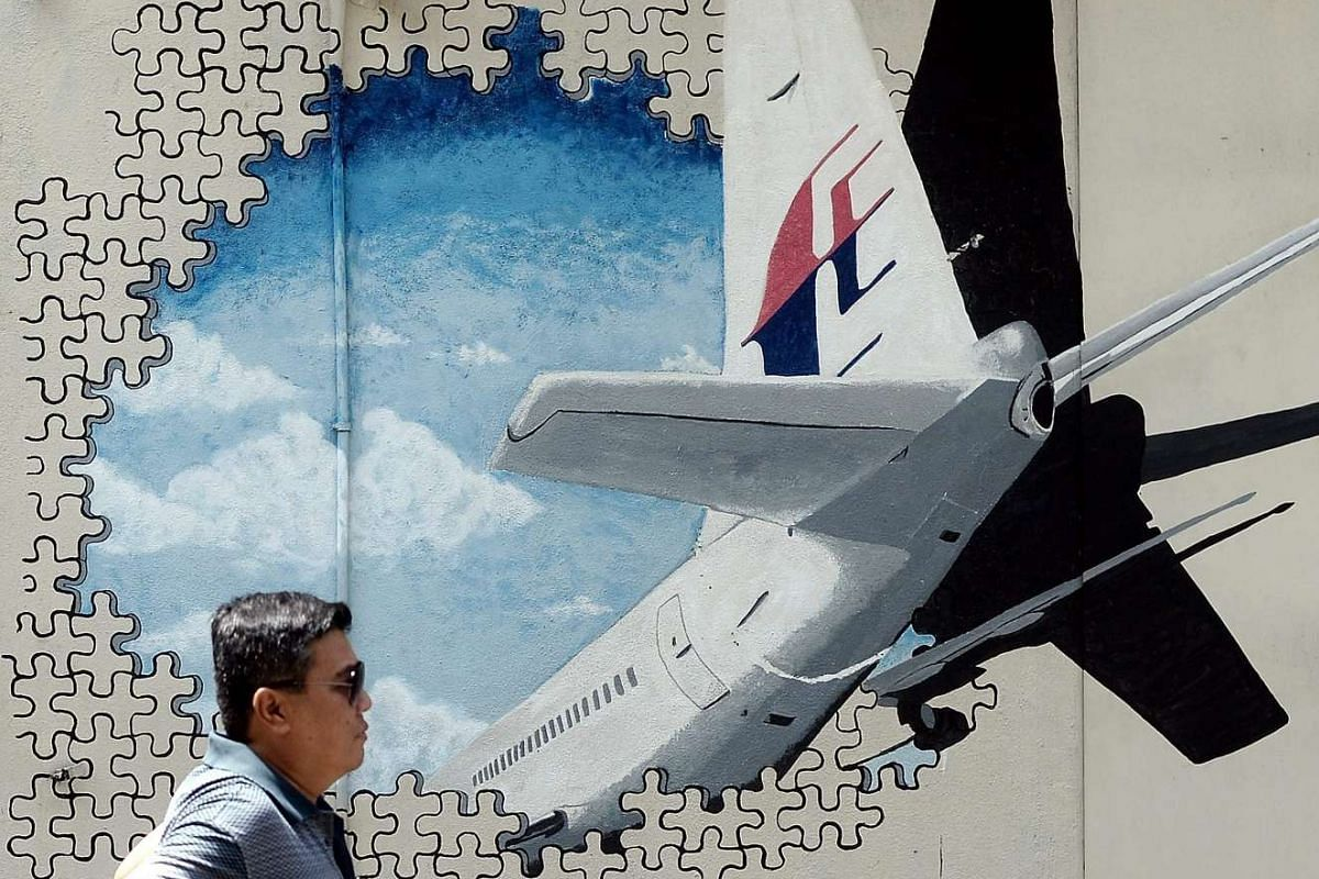 A Malaysian man walks in front of a mural of missing Malaysia Airlines MH370 plane in a back alley in Shah Alam on March 8, 2016.