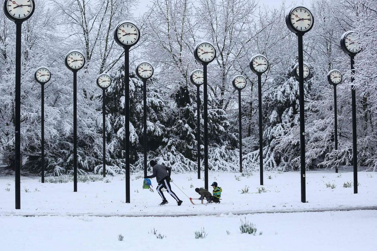 A man pulls children on a sledge a clock park made of 24 station clocks, designed by artist Klaus Rinke, in Duesseldorf, Germany, on March 7, 2016.