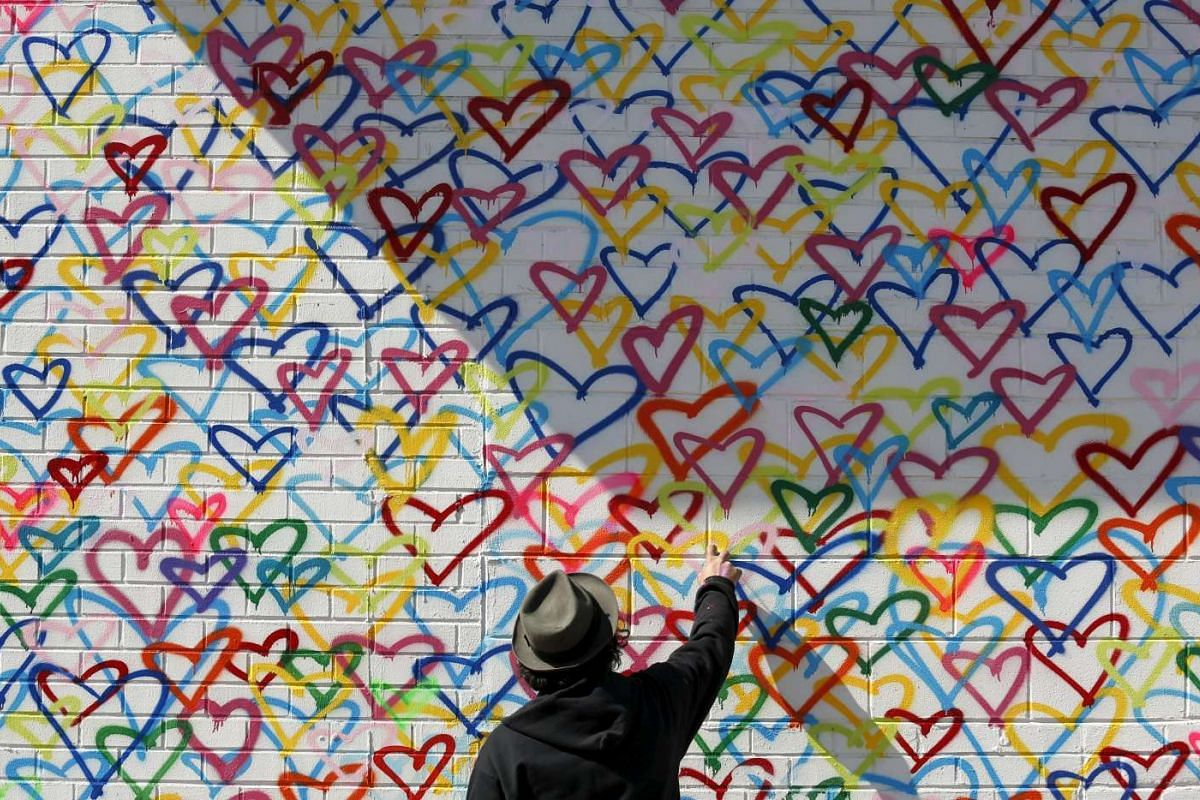 Artist Mr Brainwash adds spray paint to one of his murals during US First Lady Michelle Obama's visit to Union Market for an event celebrating International Women's Day in Washington on March 8, 2016.
