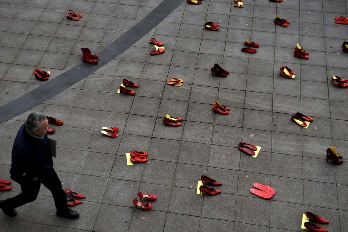 A man walks past a group of red shoes used for a performance to denounce violence against women organized by Amnesty International during International Women's Day in Gijon, Spain on March 8, 2016.