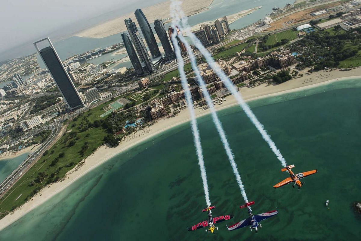 Matt Hall of Australia leading Kirby Chambliss of the United States and Nicolas Ivanoff of France over the Emirates Palace prior to the first stage of the Red Bull Air Race World Championship in the city of Abu Dhabi in the United Arab Emirates on Ma