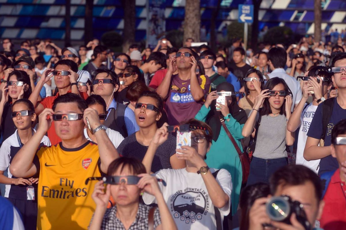 People watch the solar eclipse in Singapore on March 9, 2016.