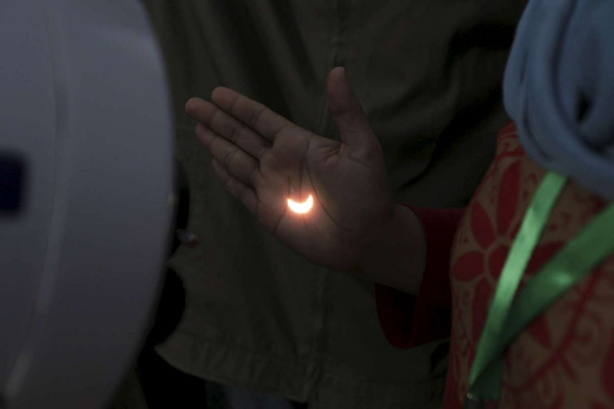 Light from a solar eclipse is reflected on a person's hand from a telescope on the Ampera Bridge over the Musi River in Palembang, South Sumatra province, Indonesia on March 9, 2016.