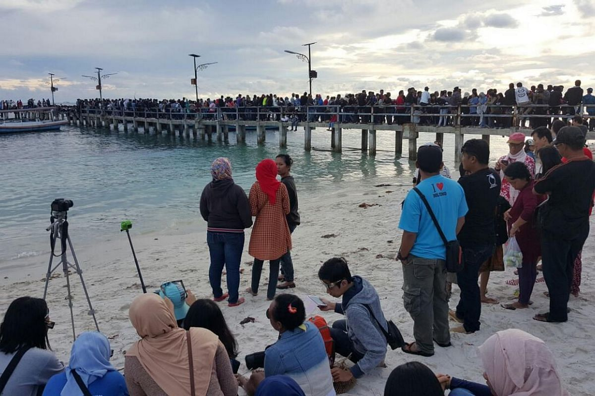 People waiting to view the solar eclipse at Tanjung Kelayang beach on the Indonesian island of Belitung.