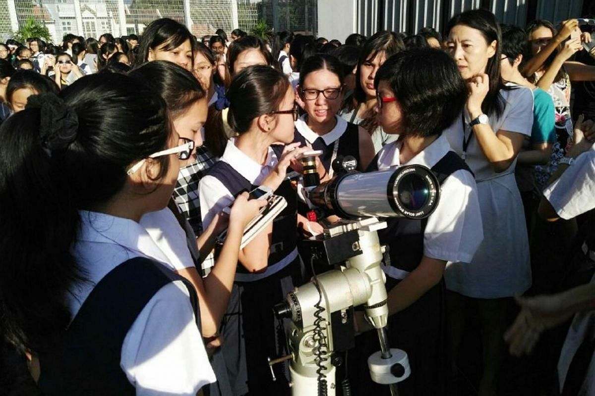 Students at Paya Lebar Methodist Girls' School (Secondary) (PLMGS) look through a telescope to view the solar eclipse on March 9, 2016.