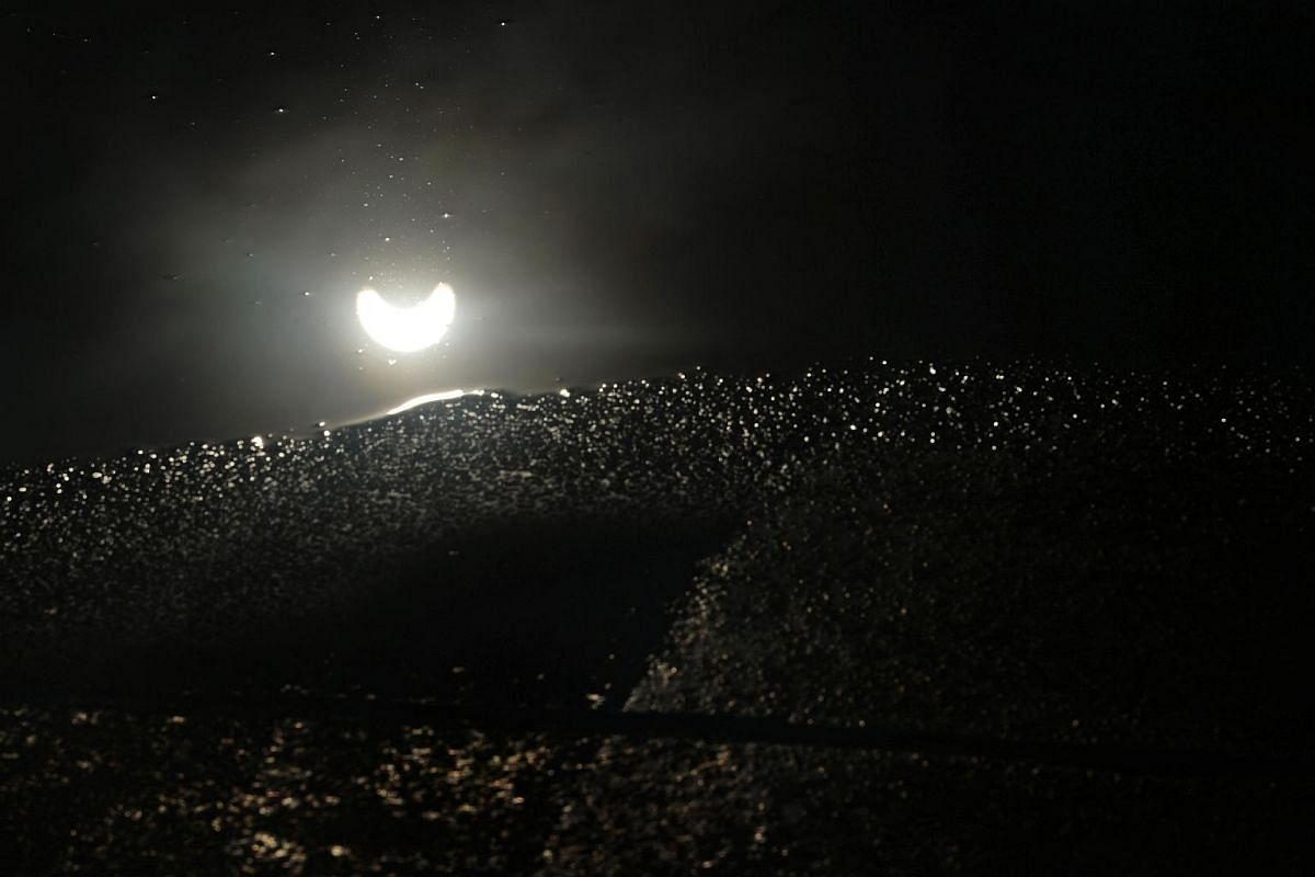 The solar eclipse is seen reflected in a puddle of water at 8.45am on March 9, 2016.