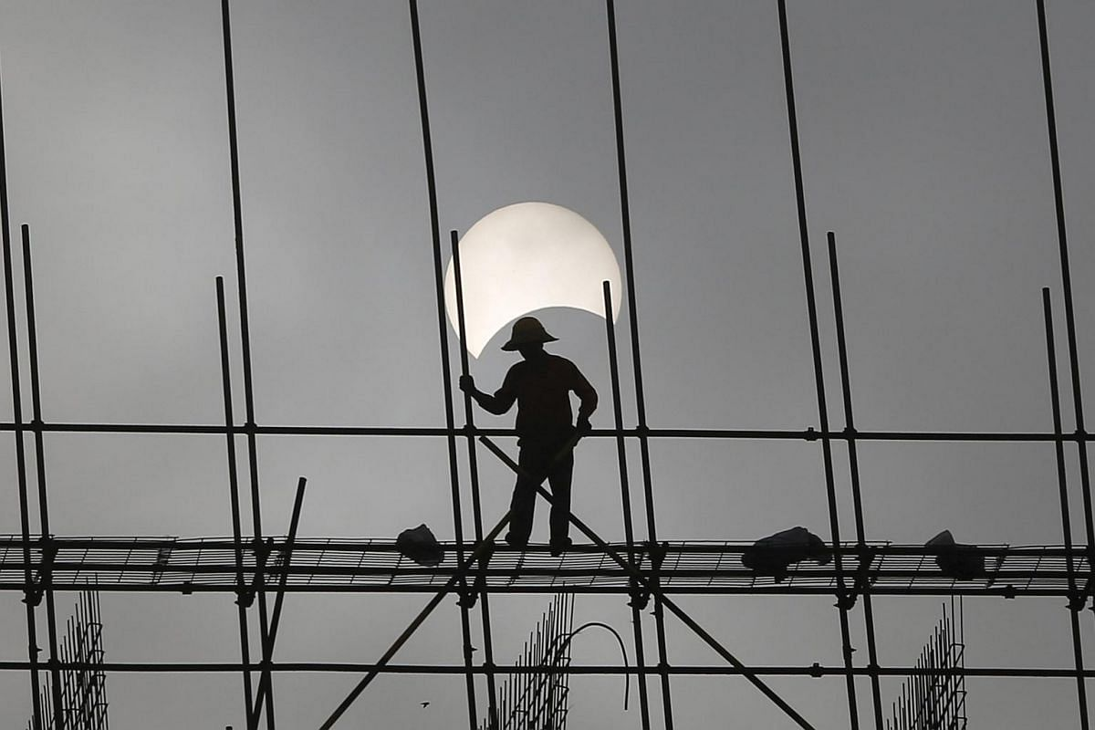 A partial solar eclipse is seen as a labourer works at a construction site in Phnom Penh, Cambodia, on March 9, 2016.