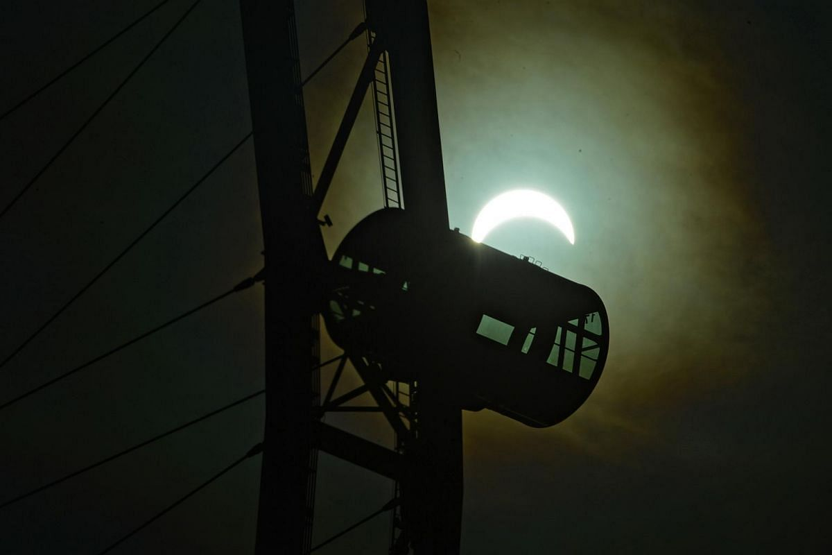 A capsule of the Singape flyer is seen in the foreground as the solar eclipse occurs, at around 8.37am on March 9, 2016.