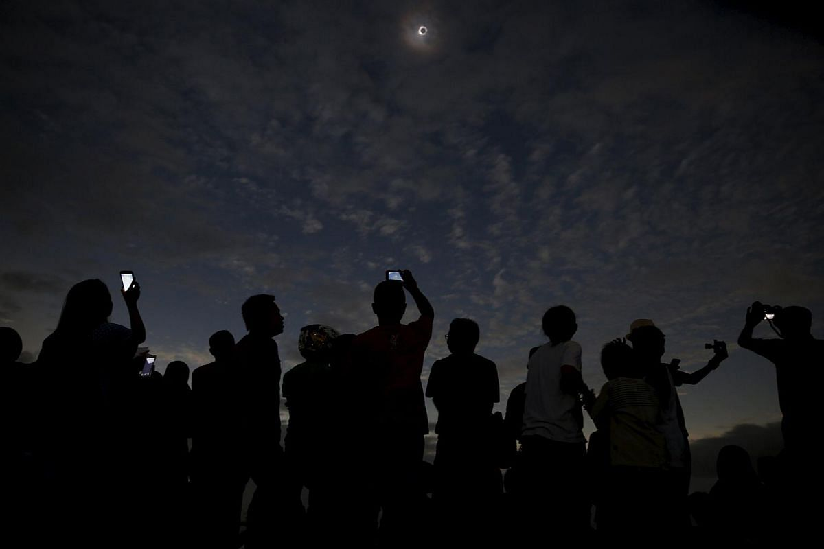 People watch and take pictures of the solar eclipse at the beach on Ternate island, Indonesia, on March 9, 2016.