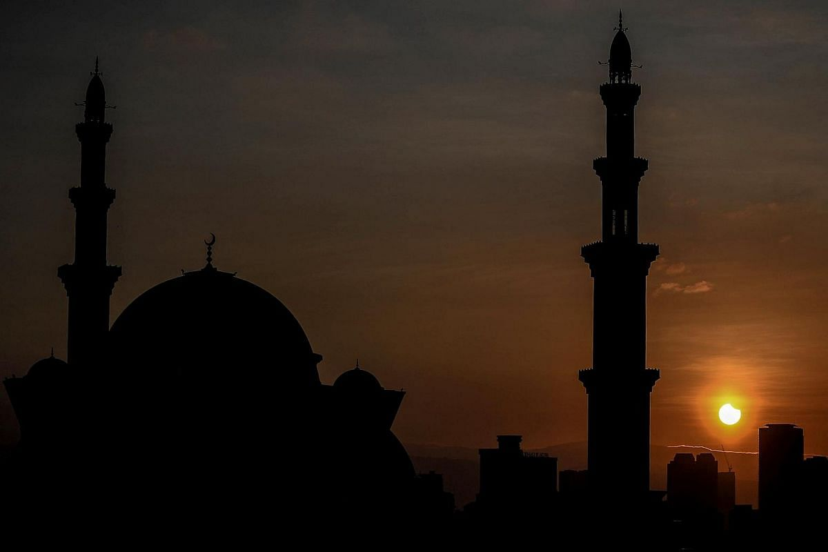 A general view shows a partial solar eclipse behind the Wilayah mosque in Kuala Lumpur on March 9, 2016.