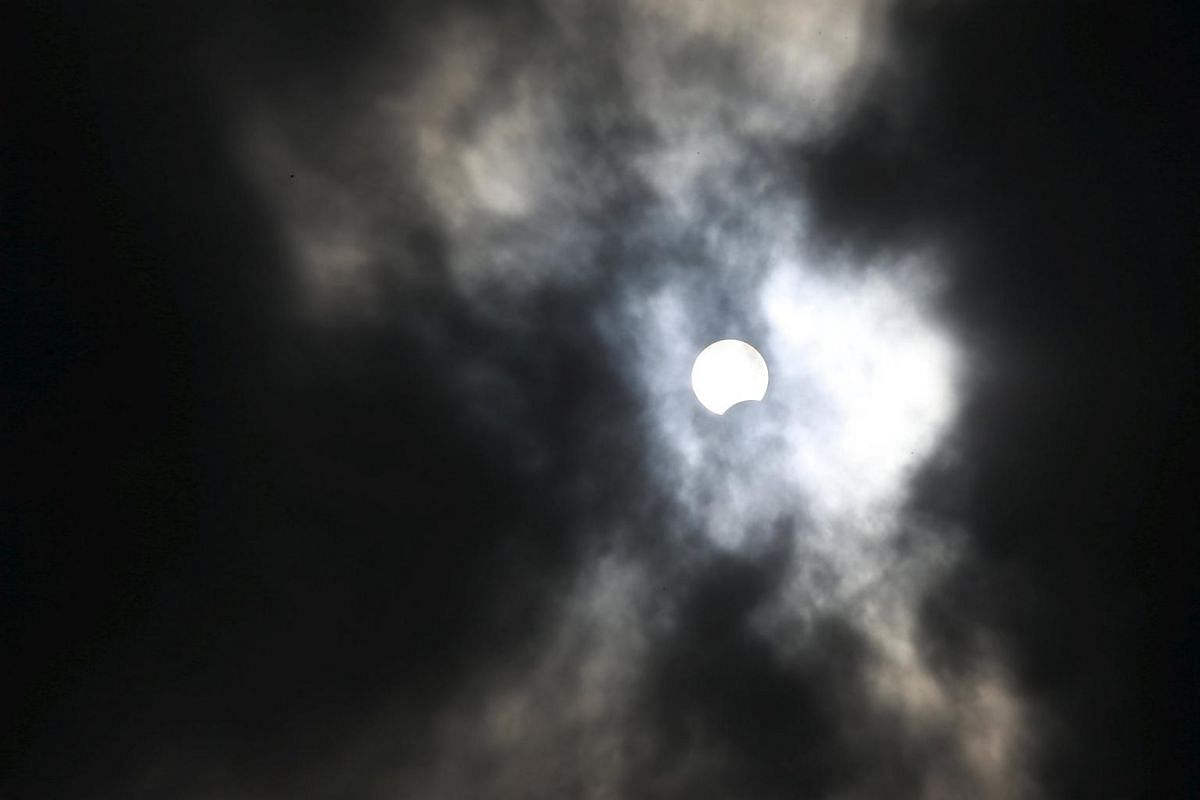 A partial solar eclipse is seen at the Bund in Shanghai, China, on March 9, 2016.