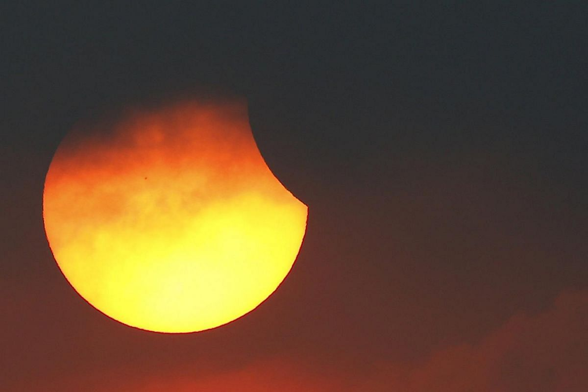 A partial solar eclipse is seen through clouds in Bangkok, Thailand, on March 9, 2016.