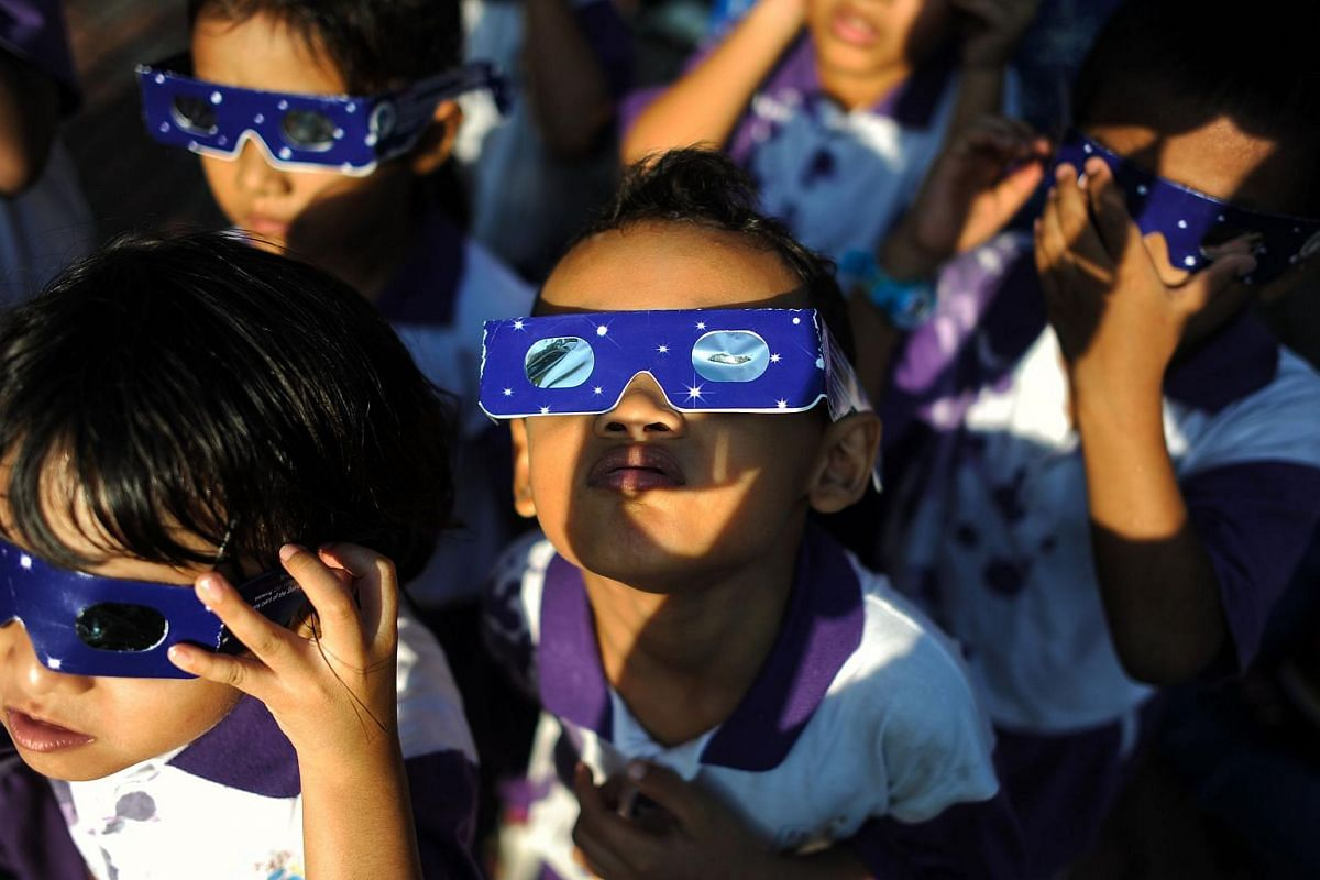Malaysian school children wearing glasses with special filters watch the partial solar eclipse at the National Planetarium in Kuala Lumpur on March 9, 2016.