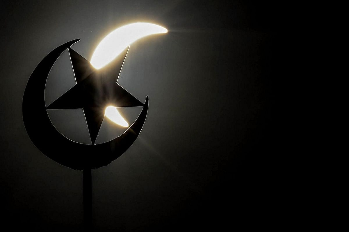 A general view shows a partial solar eclipse behind a star and crescent symbol atop a mosque in Kuala Lumpur on March 9, 2016.