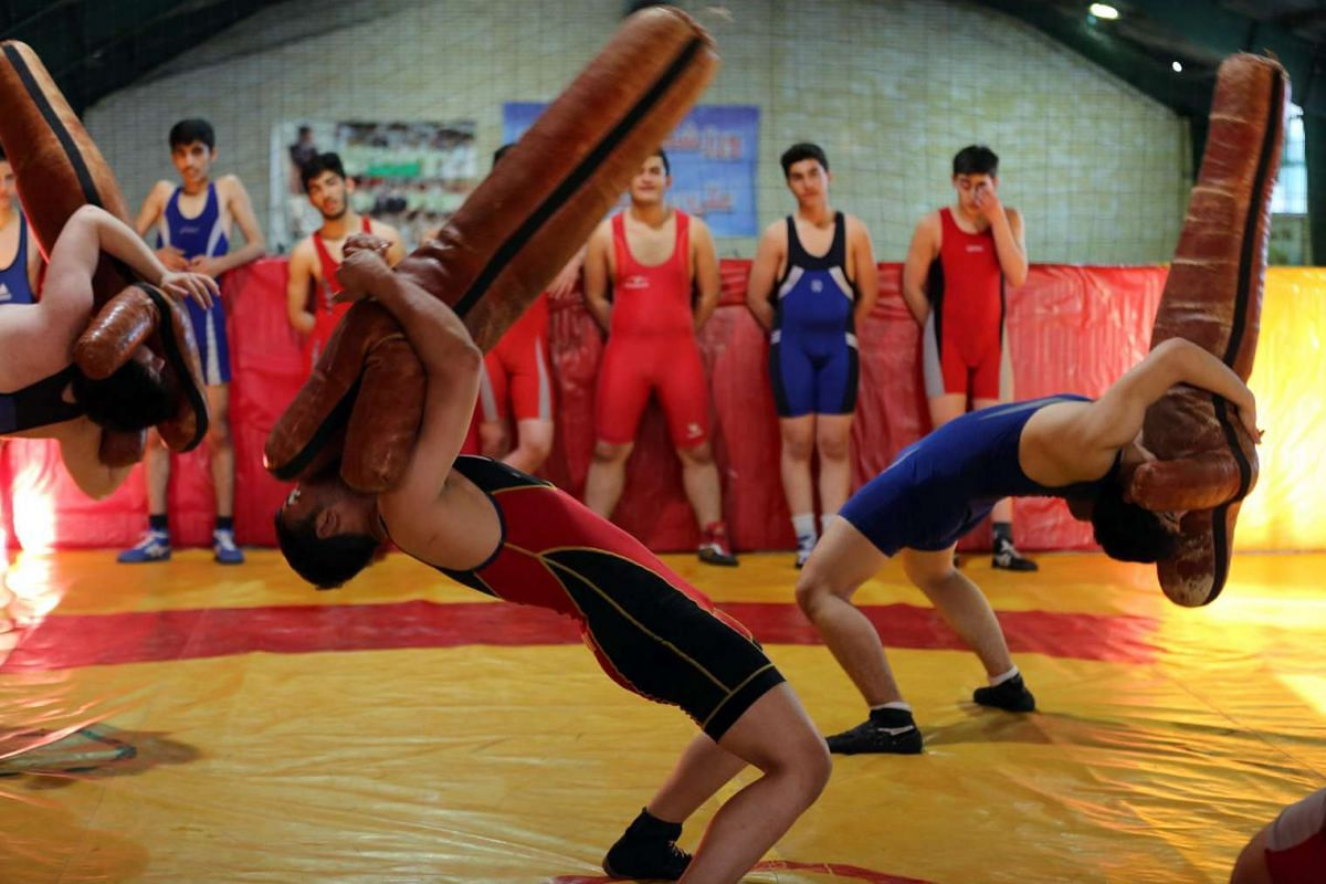 Iranian young men take part in a freestyle wrestling training session on March 7, 2016 at the West wrestling home in the capital Teheran.