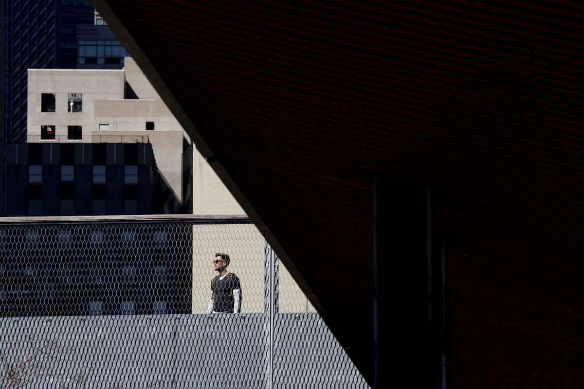 A man takes in the sunshine while standing in a park in lower Manhattan during a spell of unseasonably warm temperatures in New York, USA on March 9, 2016.