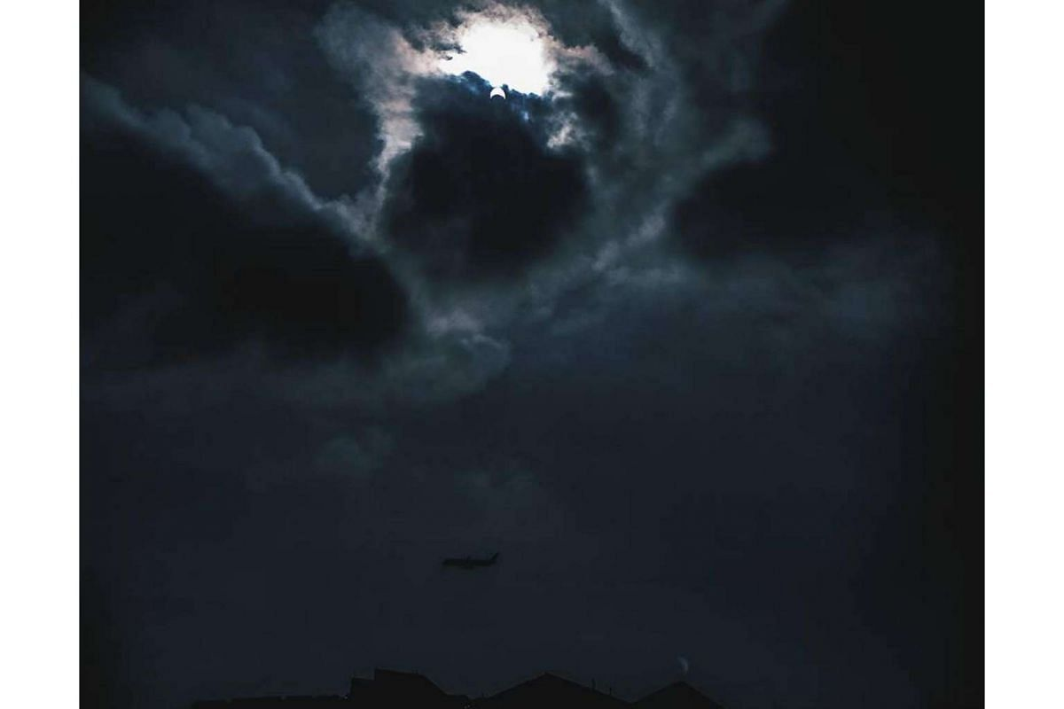 ST reader Danish Danial sent in this picture of the solar eclipse from Changi, with a plane landing at the airport.