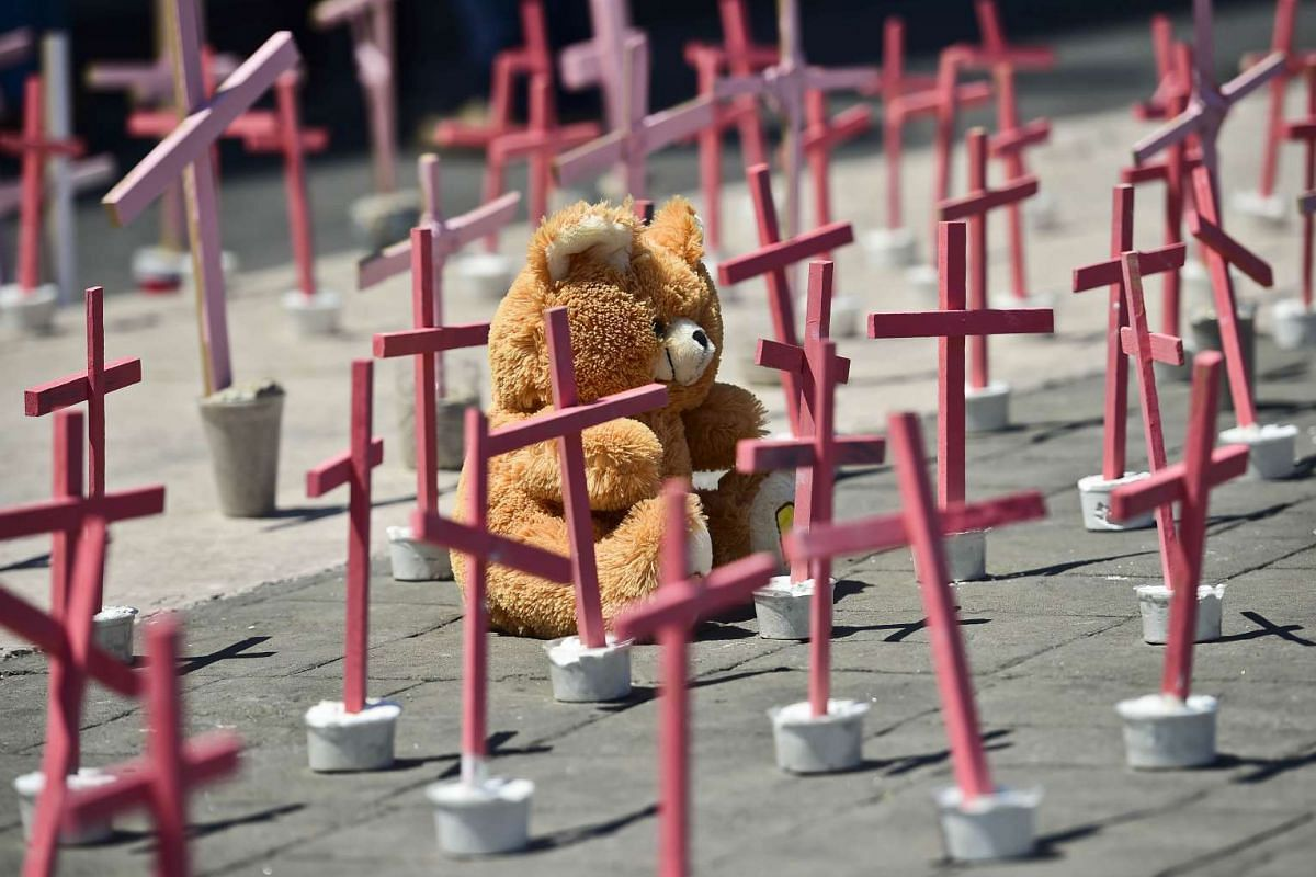 A wooly bear from a victim of femicide are pictured next to crosses during a protest against the murder of more than 600 women in the last four years, in Ecatepec, State of Mexico, on March 13 , 2016. PHOTO: AFP