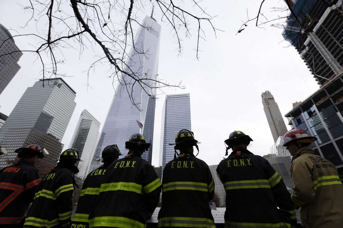 New York City firemen and firefighters from across the globe are seen during a moment of silence for their fallen comrades at the 9/11 memorial reflecting pool before the start of the 2nd Annual New York City Firefighter Stair Climb at 4 World Trade
