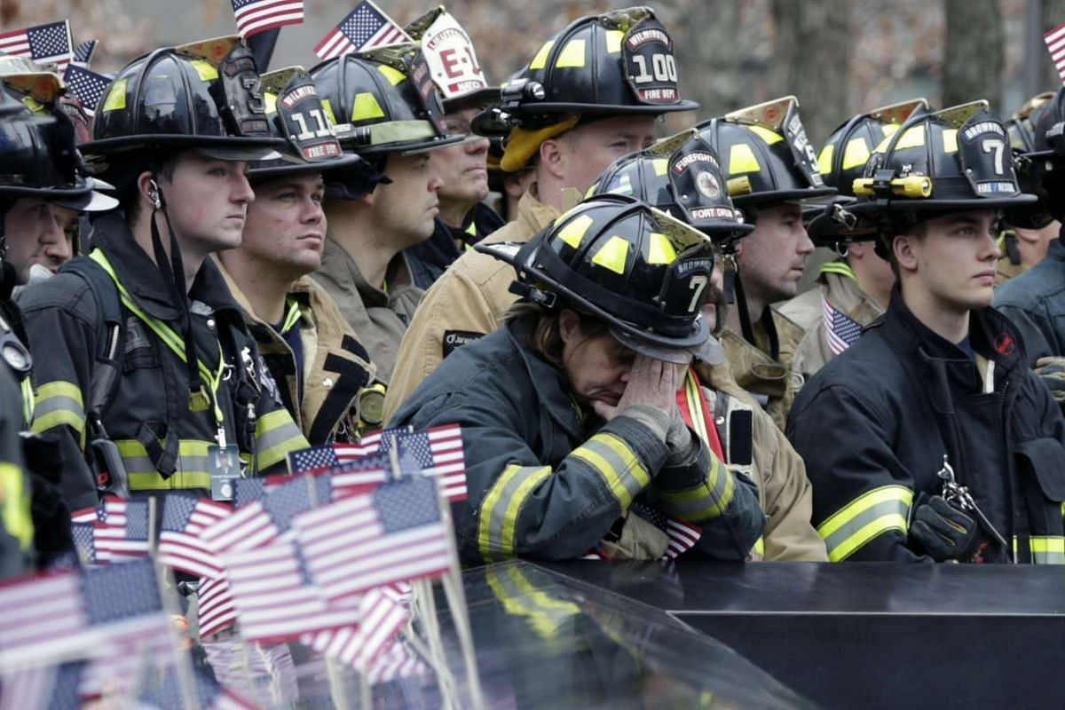 A firefighter (centre) prays with other firefighters from across the globe during a moment of silence for their fallen comrades at the 9/11 memorial reflecting pool before the start of the 2nd Annual New York City Firefighter Stair Climb at 4 World T