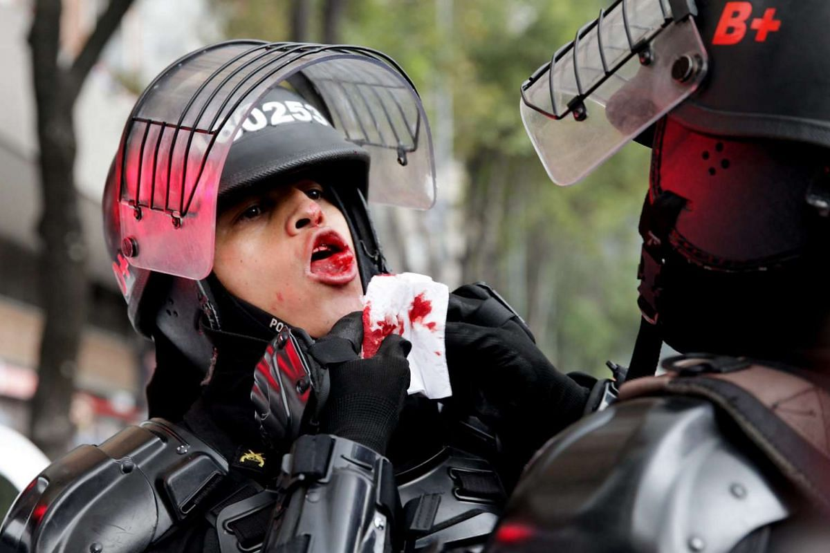 An anti-riot police officer is assisted after getting hurt during a taxi drivers' protest against car sharing application Uber in Bogota, Colombia, March 14, 2016. PHOTO: EPA