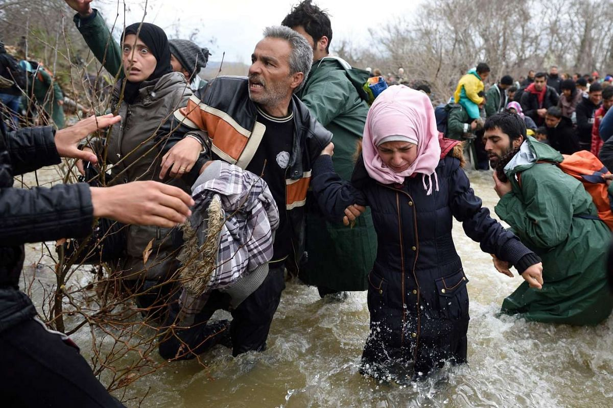 Refugees and migrants try to cross a river on their way to Macedonia from a makeshift camp at the Greek-Macedonian border, near the Greek village of Idomeni on March 14, 2016, PHOTO: AFP