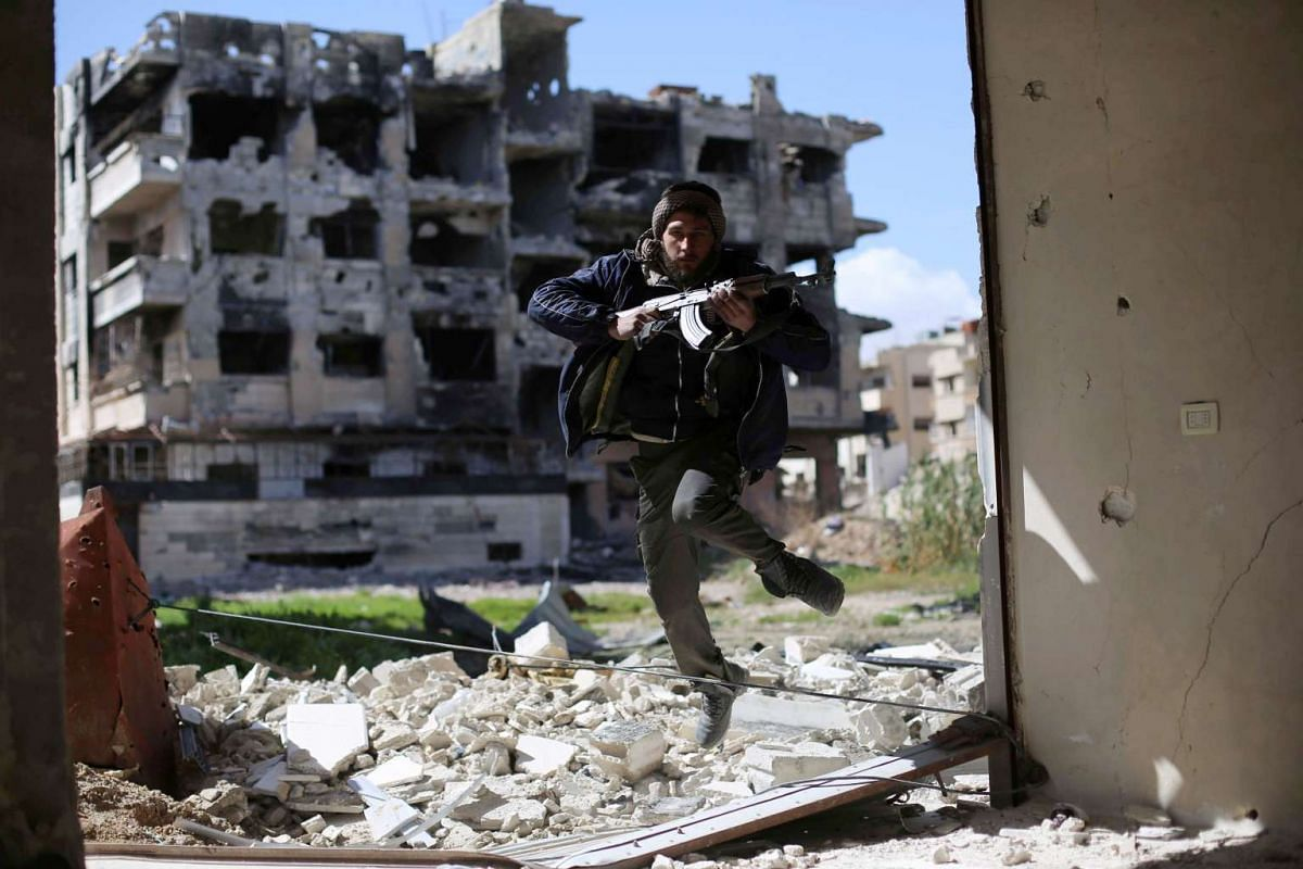 A fighter belonging to Jaish al-Islam (Islam Army) runs to take cover near the frontline on March 14, 2016 in the neighbourhood of Jobar, on the eastern outskirts of the capital Damascus. PHOTO: AFP