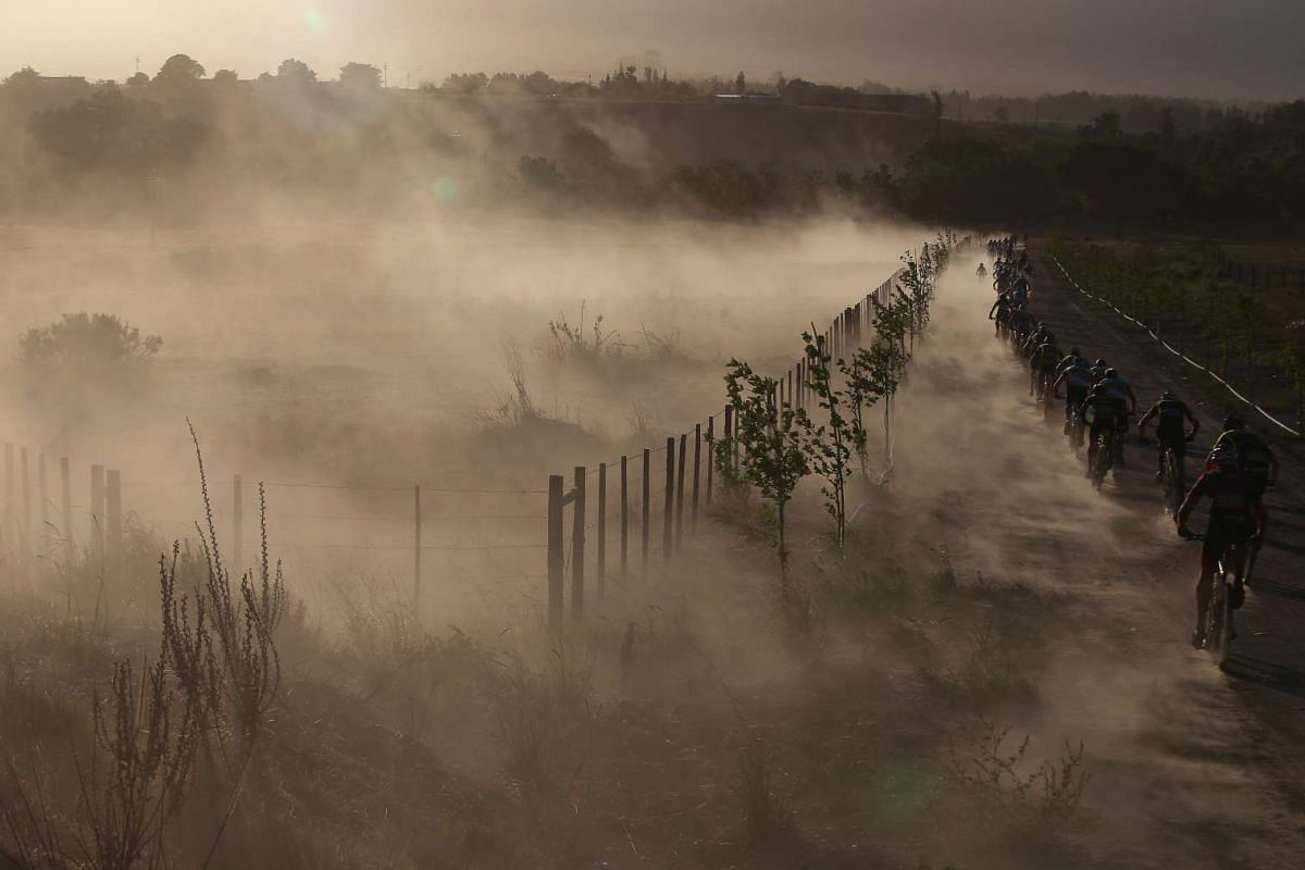 Cyclists kick up dust as they ride in the early morning light of the 108km Stage 1 of the 2016 ABSA Cape Epic mountain bike race in Saronsberg South Africa, March 14, 2016. PHOTO: EPA