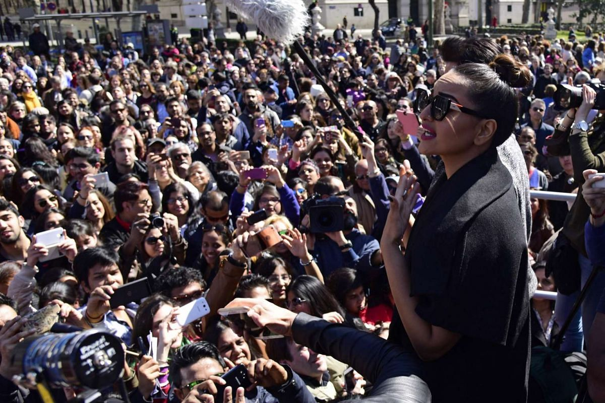 Indian actress Sonakshi Sinha (right) greets fans during a Bollywood flashmob in Madrid, on March 13, 2016.