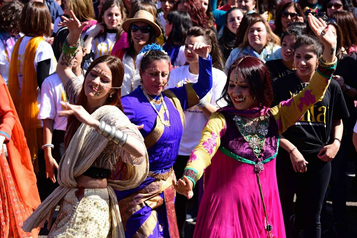 Dancers perform during a Bollywood flashmob on the Paseo del Prado, in front of the Palacio de Cibeles in Madrid, on March 13, 2016.