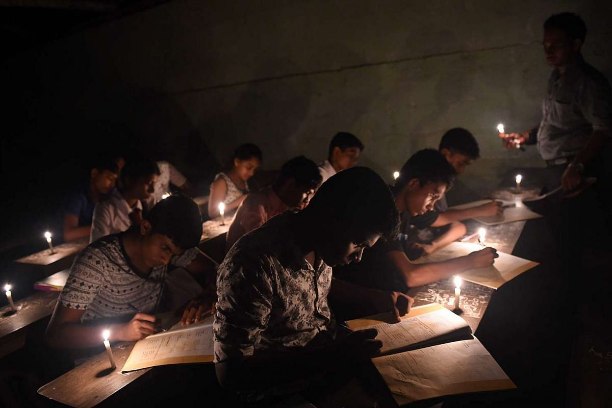 Sri Lankan students work in classes lit by candles after a power cut in Biyagama, a suburb of the capital Colombo, on March 15, 2016. PHOTO: AFP