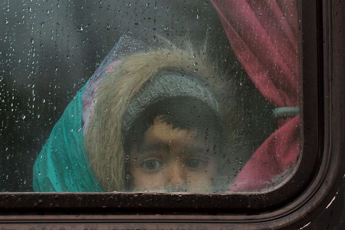 A child looks out of a bus window as refugees are returned to a makeshift camp at the Greek-Macedonian border, near the Greek village of Idomeni, on March 15, 2016, where thousands of refugees and migrants are stranded by the Balkan border blockade.
