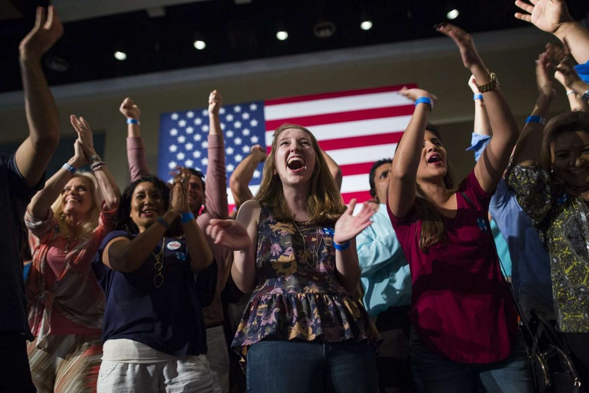 Supporters of Democratic presidential candidate Hillary Clinton cheer at the site of early poll numbers coming out of Florida, which have Hillary ahead of rival Bernie Sanders, on March 15, 2016.
